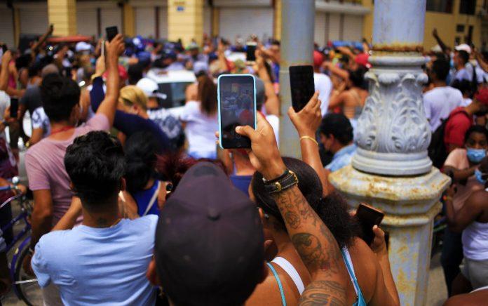 Un joven graba con su teléfono móvil la actuación policial durante las manifestaciones del 11 de julio en La Habana. Foto: Rialta.